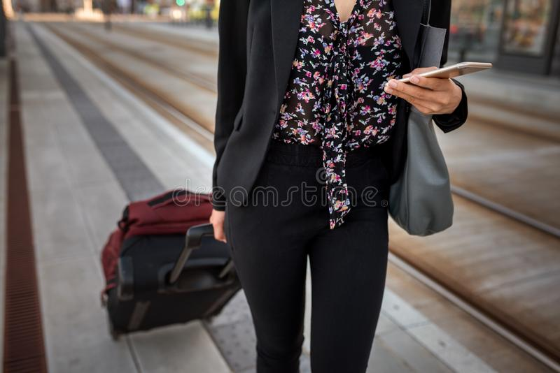 Onderneemster met zakken die haar cellphone gebruiken bij een trameinde stock foto
