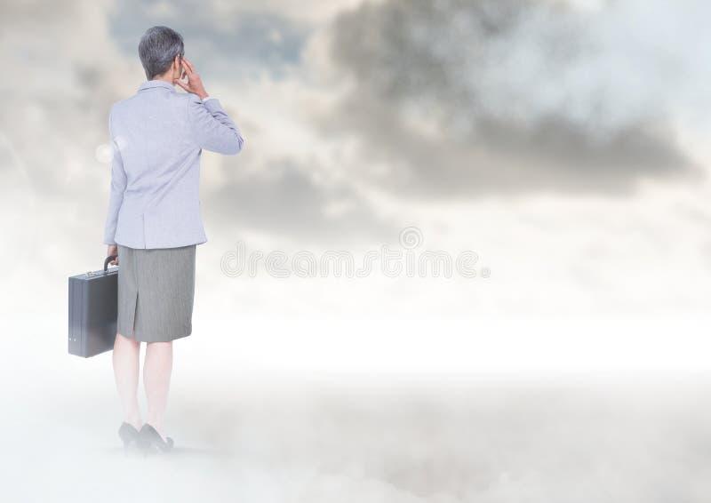 Onderneemster onder hemelwolken met aktentas royalty-vrije stock afbeelding