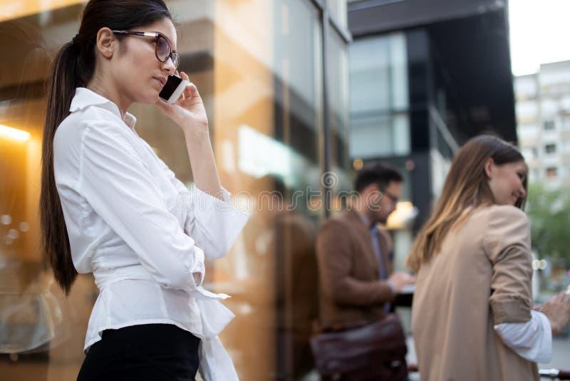 Onderneemster op de telefoon Vrouw die haar telefoon op haar manier van het werk met behulp van stock fotografie