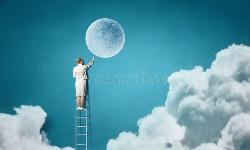 Onderneemster op ladder die maan bereiken royalty-vrije stock afbeelding