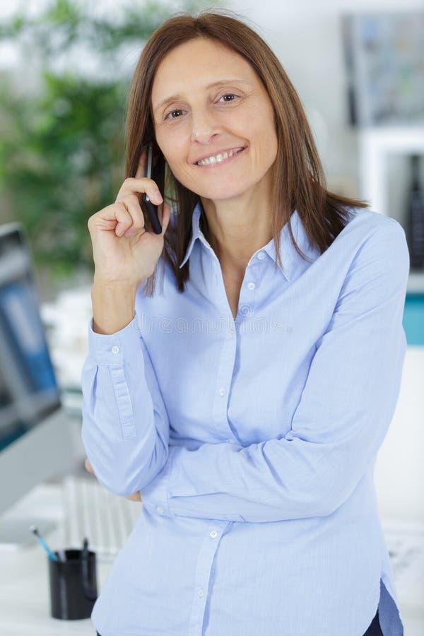 Onderneemster op telefoon in bureau royalty-vrije stock afbeeldingen