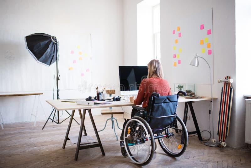 Onderneemster in rolstoel bij het bureau in haar bureau royalty-vrije stock afbeelding