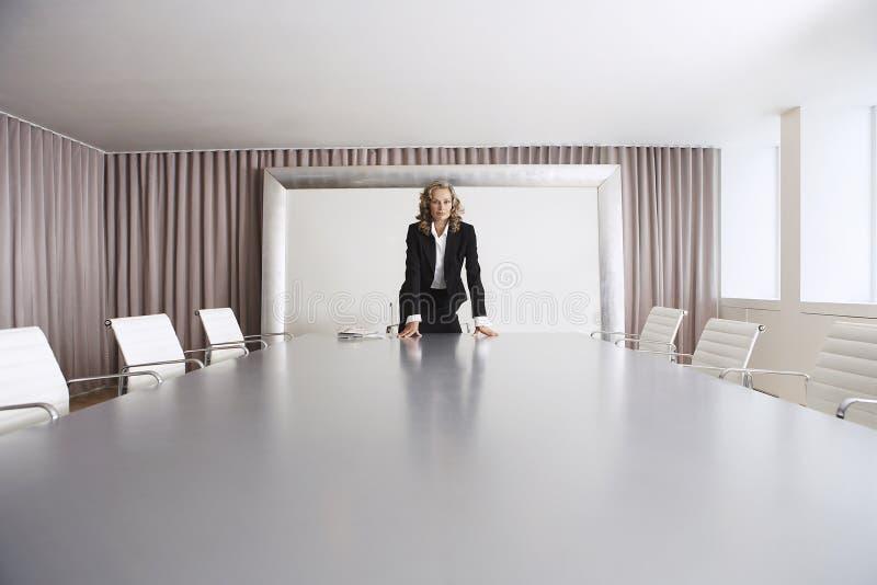 Onderneemster Standing In Boardroom stock afbeeldingen