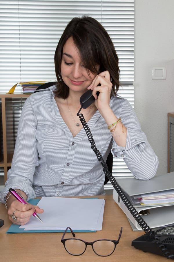 Onderneemster in telefoon met klant op kantoor royalty-vrije stock fotografie