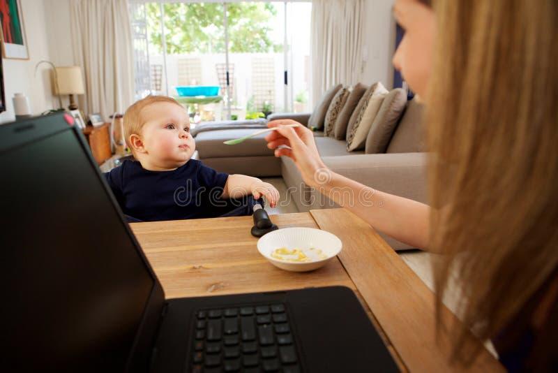 Onderneemster thuis en voedende baby die werken royalty-vrije stock afbeeldingen