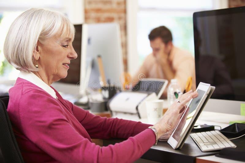 Onderneemster Using Digital Tablet in Creatief Bureau stock foto's