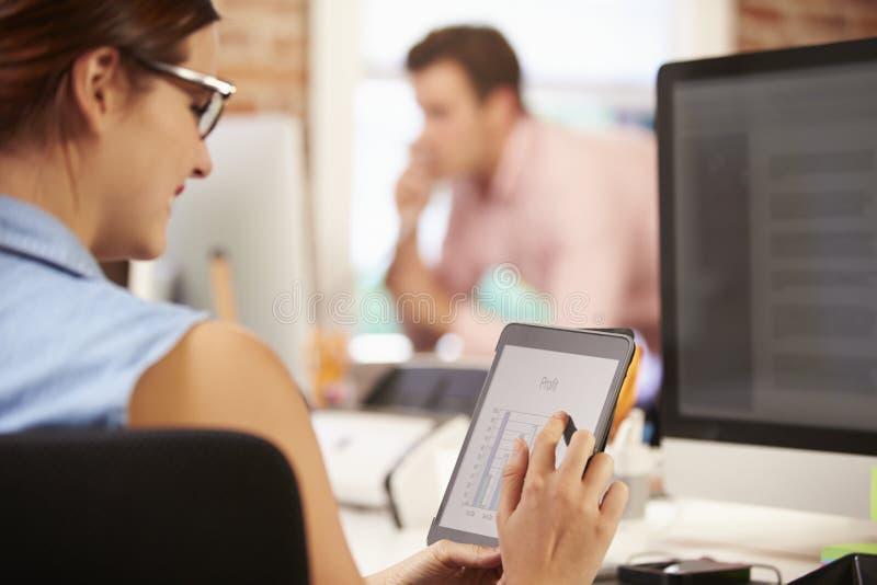 Onderneemster Using Digital Tablet in Creatief Bureau royalty-vrije stock afbeelding