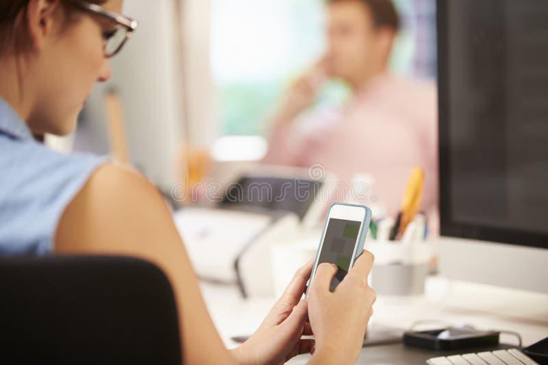 Onderneemster Using Mobile Phone in Creatief Bureau stock afbeeldingen