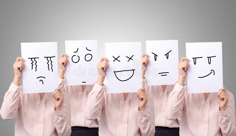 Onderneemster vijf die een kaart met verschillend de emotiegevoel van tekeningsgelaatsuitdrukkingen houden ziet op Witboek onder  stock foto