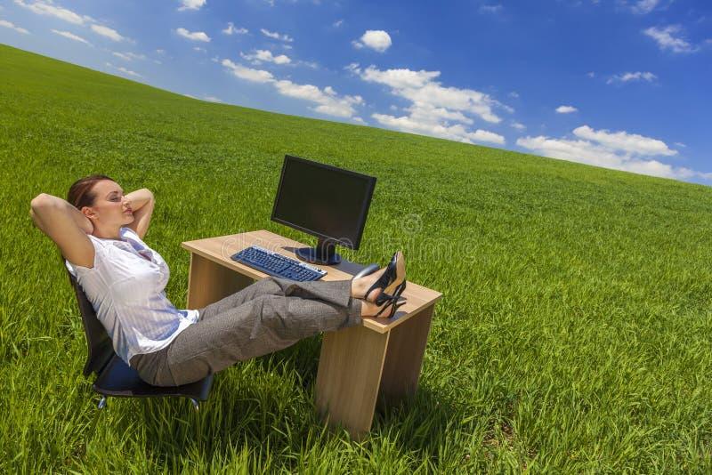 Onderneemster Woman Relaxing bij Bureau op Groen Gebied stock afbeelding