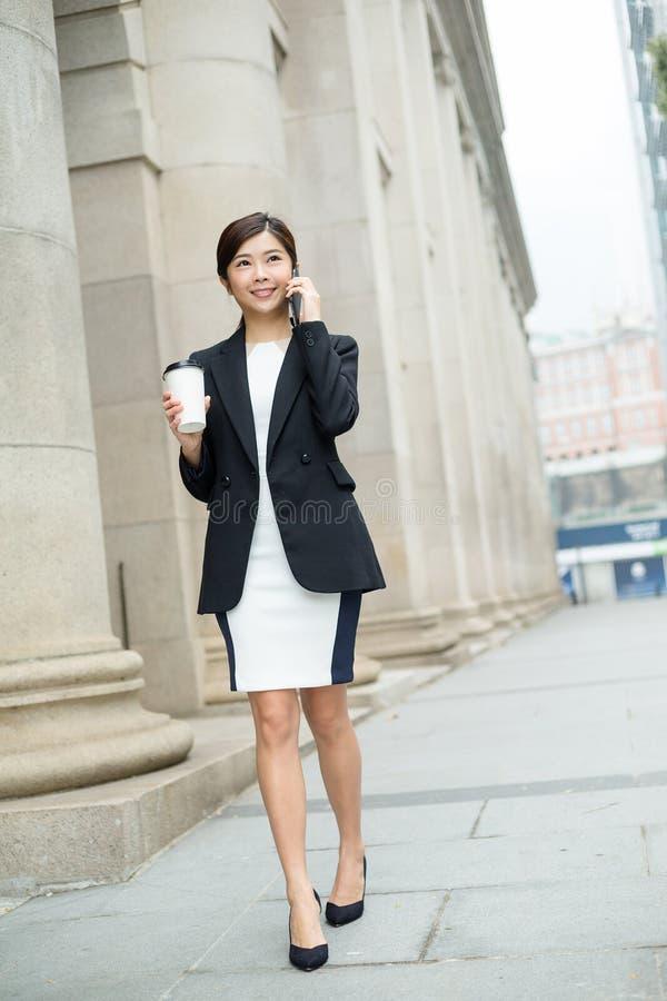 Onderneemsterbespreking aan mobiele telefoon en het lopen bij straat royalty-vrije stock fotografie