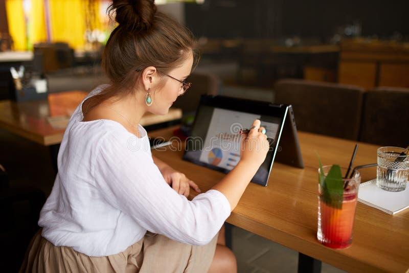 Onderneemsterhand die met naald op de grafiek over het convertibele laptop scherm op tentwijze richten Vrouw die 2 in 1 gebruiken stock afbeelding
