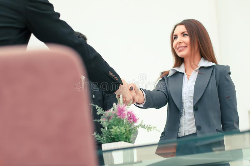 Onderneemsterhanddruk met partner in modern bureau stock afbeelding