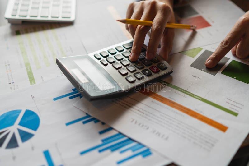 Onderneemsterhanden pen houden die werkend met calculator aan calc stock afbeelding