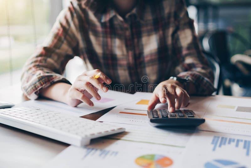 Onderneemsterhanden pen houden die werkend met calculator voor cal stock fotografie
