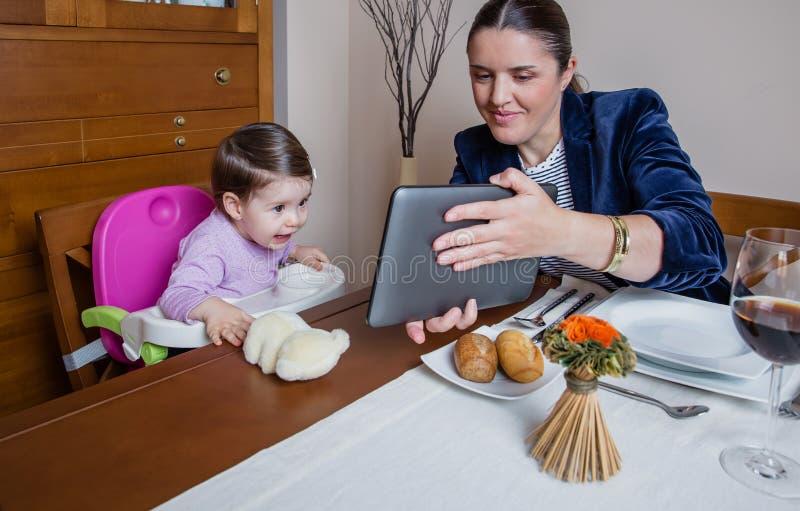 Onderneemstermoeder en babymeisje die tablet kijken royalty-vrije stock afbeeldingen