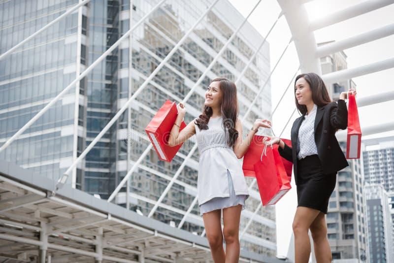 Onderneemsters die bij winkelcomplex en kleinhandelszak in stedelijk winkelen stock afbeelding