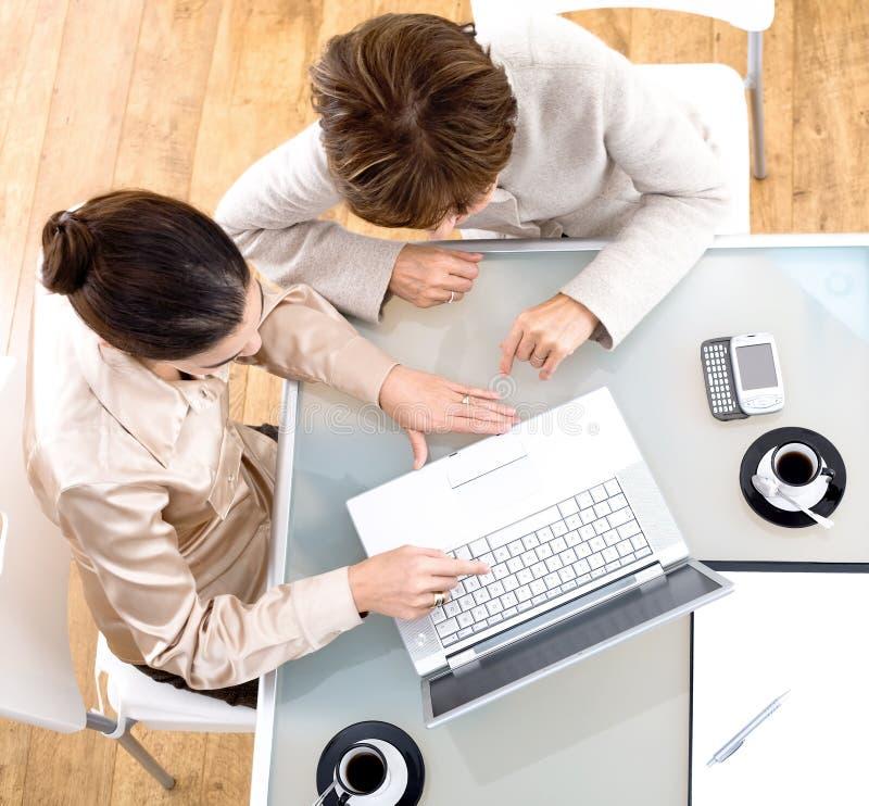 Onderneemsters die laptop computer met behulp van royalty-vrije stock foto's