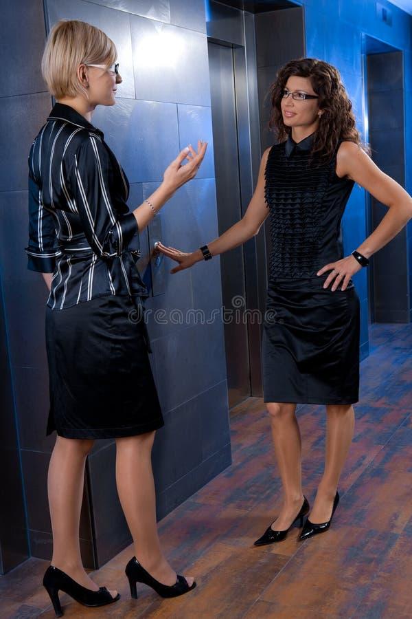 Onderneemsters die op lift wachten stock afbeelding