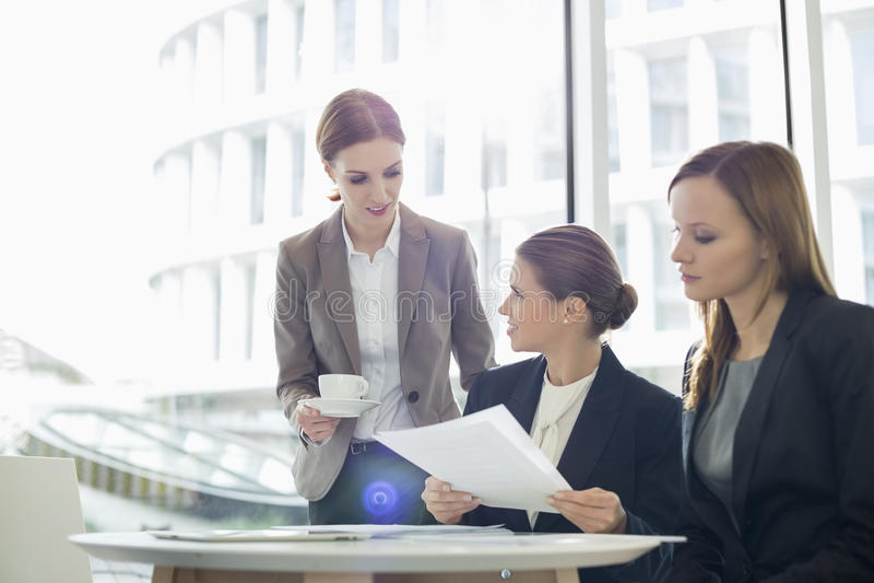 Onderneemsters met administratie tijdens koffiepauze stock foto's