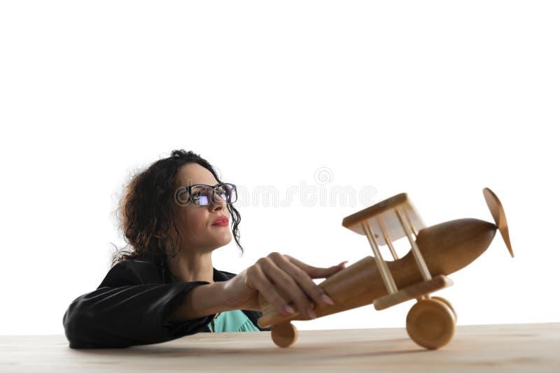 Onderneemsterspel met een stuk speelgoed vliegtuig Concept bedrijfopstarten en bedrijfssucces Ge?soleerdj op witte achtergrond royalty-vrije stock afbeelding
