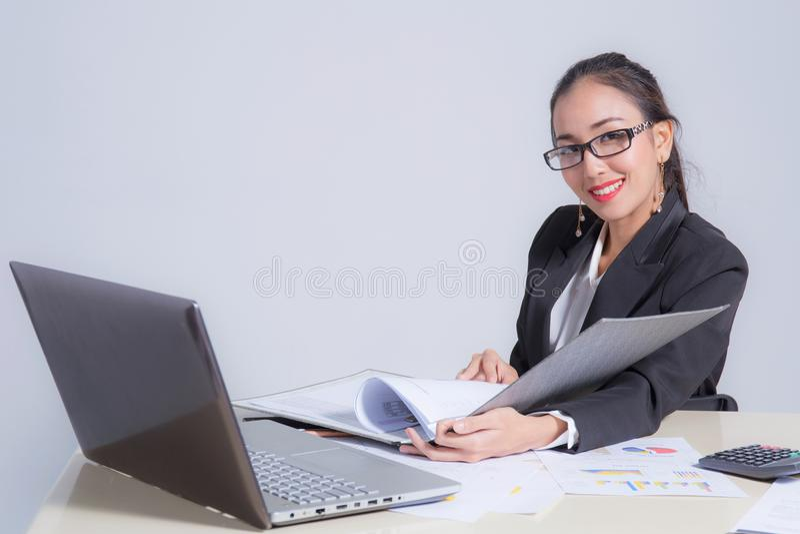 Onderneemsterzitting bij bureau in bureau Hij bekijkt de camera en het glimlachen royalty-vrije stock foto
