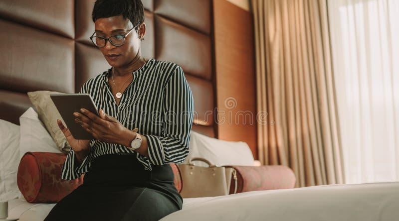 Onderneemsterzitting op bed dat digitale tablet gebruikt stock afbeeldingen