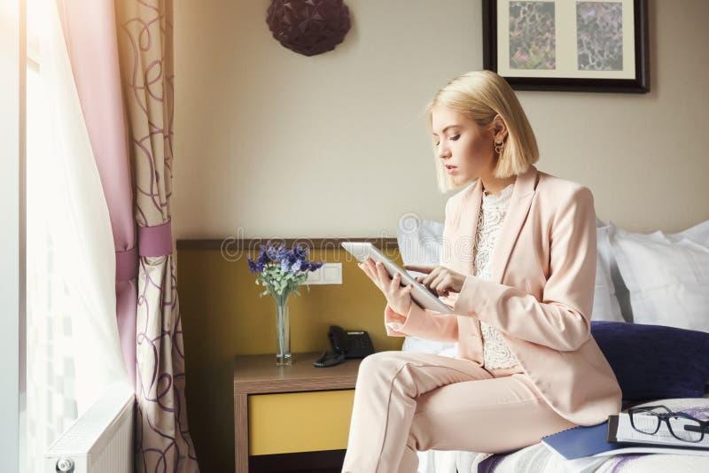 Onderneemsterzitting op bed en het gebruiken van tablet royalty-vrije stock fotografie
