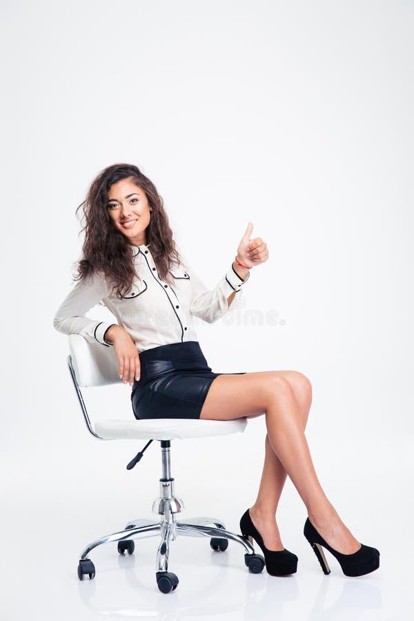 Onderneemsterzitting op de bureaustoel en het tonen van duim stock foto