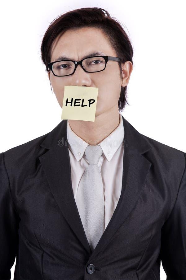 Ondernemer die een hulptekst op mond vastmaken stock foto's