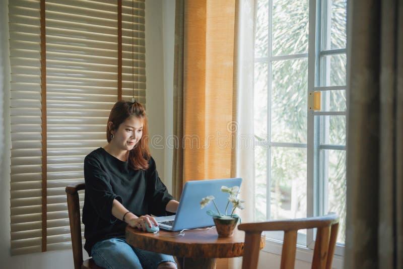 Ondernemers Aziatische vrouw die met laptop thuis werken stock afbeelding