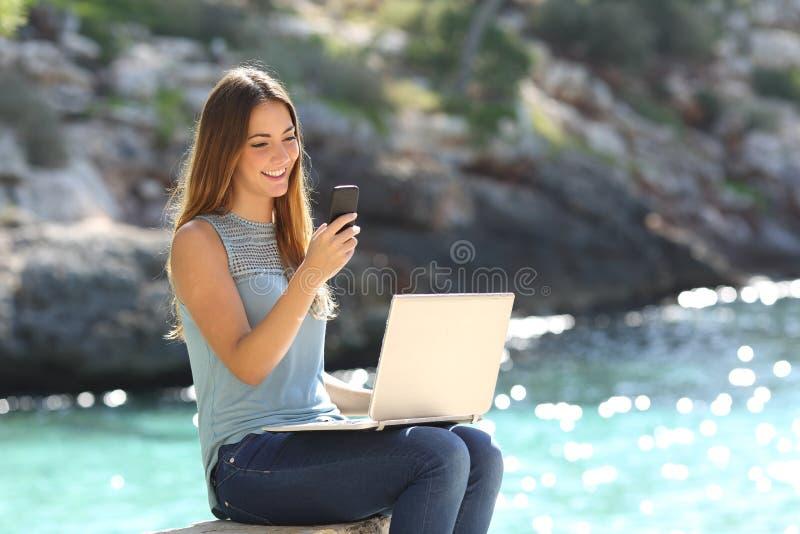 Ondernemersvrouw die met een telefoon en laptop werken royalty-vrije stock fotografie