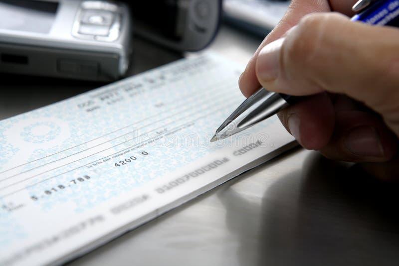 Onderteken een cheque stock foto's