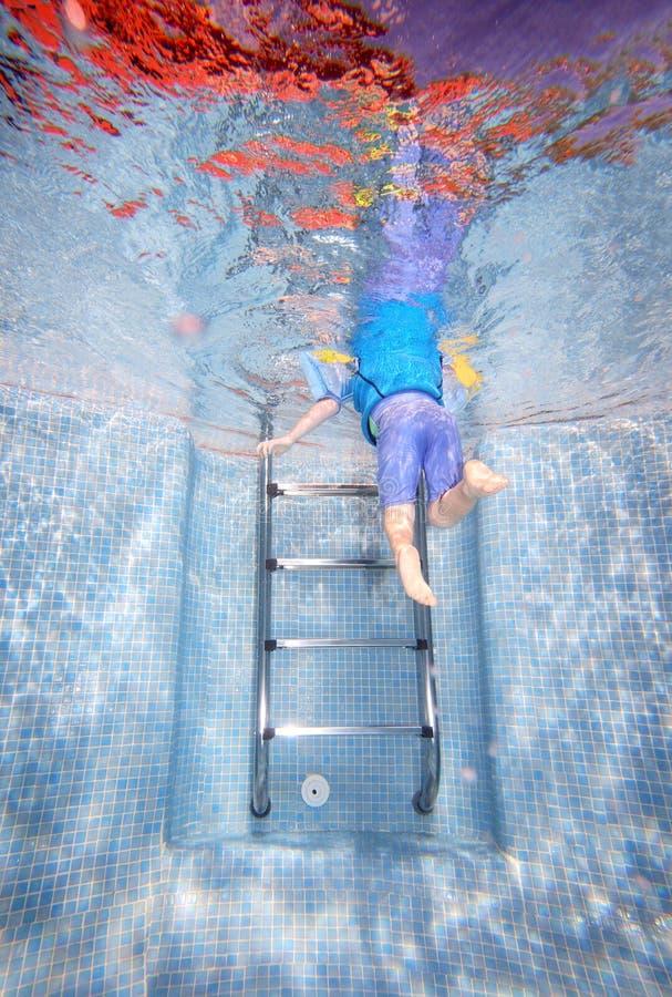 Onderwater foto van het jonge jongen beklimmen uit zwembad royalty-vrije stock afbeelding