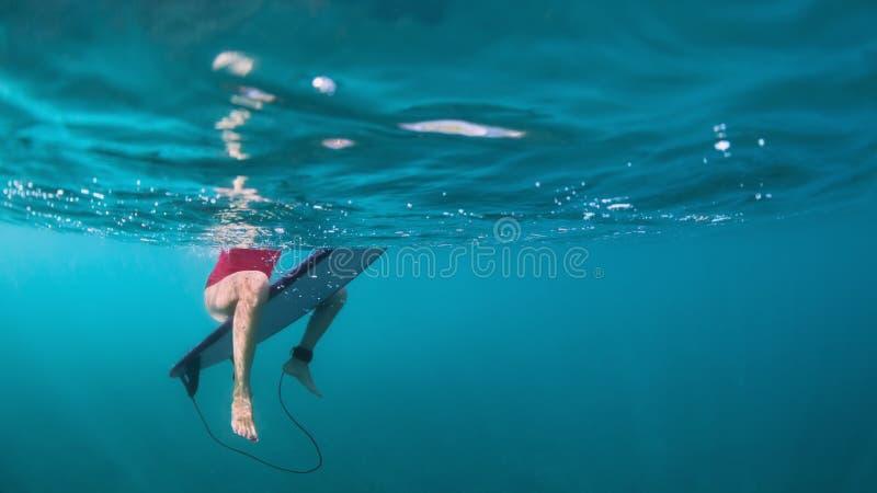Onderwaterfoto van surfermeisje op brandingsraad in oceaan royalty-vrije stock afbeeldingen