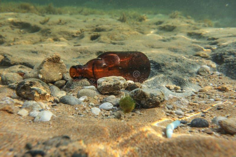 Onderwaterfoto, verworpen nietigheidfles op zeebodem Oceaan het een rommel maken van concept royalty-vrije stock afbeelding
