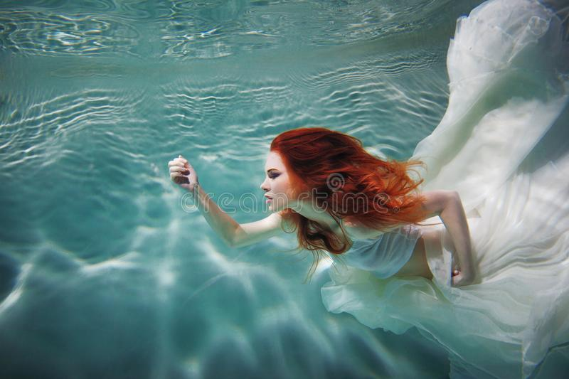 Onderwatermeisje Mooie roodharige vrouw in een witte kleding, die onder water zwemmen stock foto's
