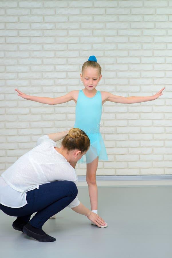 Onderwijs in balletschool De leraar verbetert stelt van weinig ballerina in klasse Leuk meisje tijdens danspraktijk royalty-vrije stock afbeelding