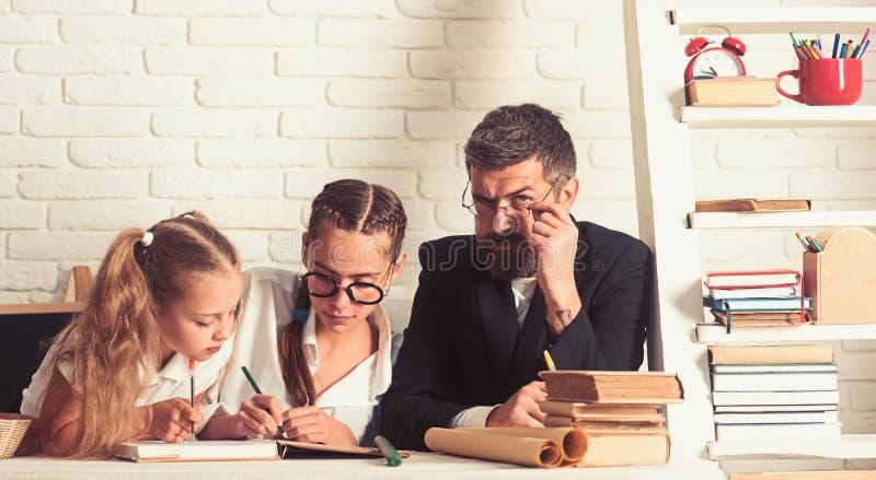 Onderwijs en kennisdag Terug naar school en huis het scholen De vader helpt kinderen thuis te bestuderen Schooltijd van royalty-vrije stock afbeeldingen