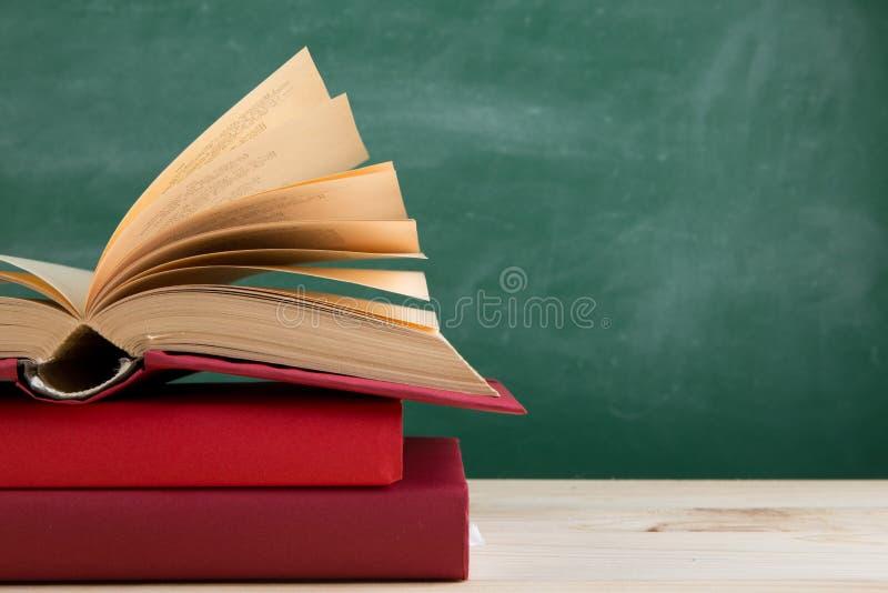 Onderwijs en lezingsconcept - groep kleurrijke boeken op de houten lijst in het klaslokaal, bordachtergrond stock afbeelding