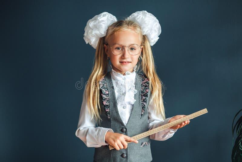 Onderwijs en schoolconcept Het schoolmeisje, blonde in school eenvormig met witte bogen en glazen houdt heerser op blauwe achterg royalty-vrije stock afbeelding