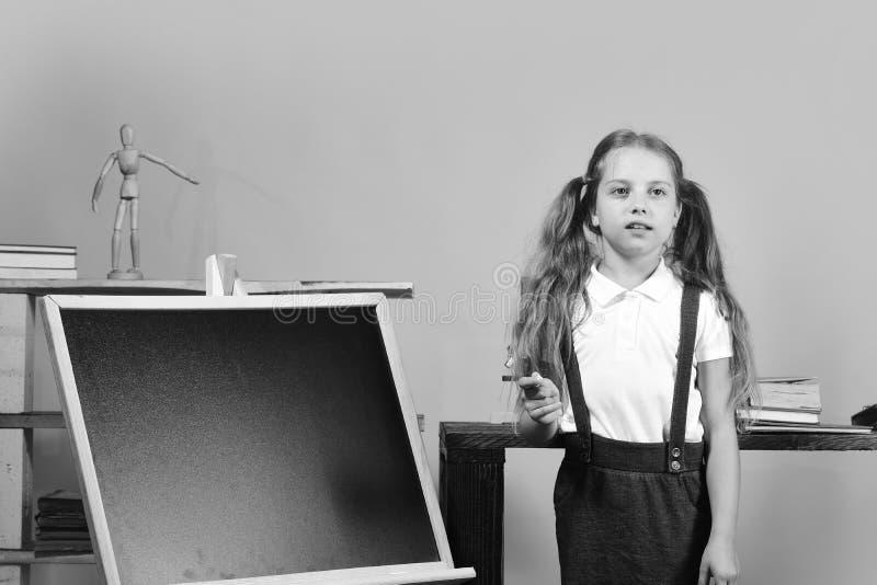 Onderwijs en terug naar schoolconcept Het meisje schrijft op bord, exemplaarruimte Schoolmeisje met nadenkend gezicht stock fotografie