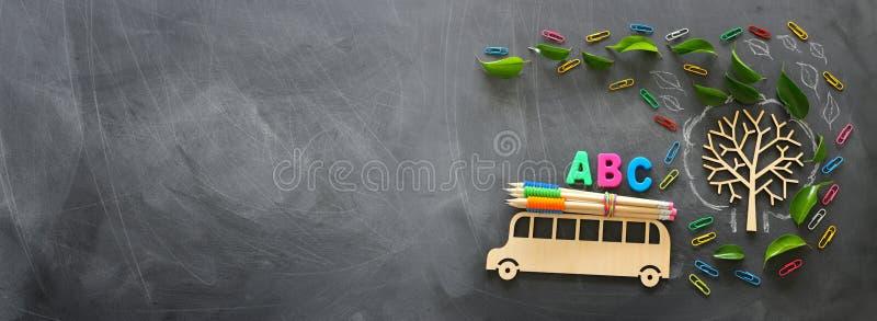 Onderwijs en terug naar schoolconcept Hoogste meningsfoto van houten bus en ABC-brieven, potloden op het dak naast boom met de he stock foto