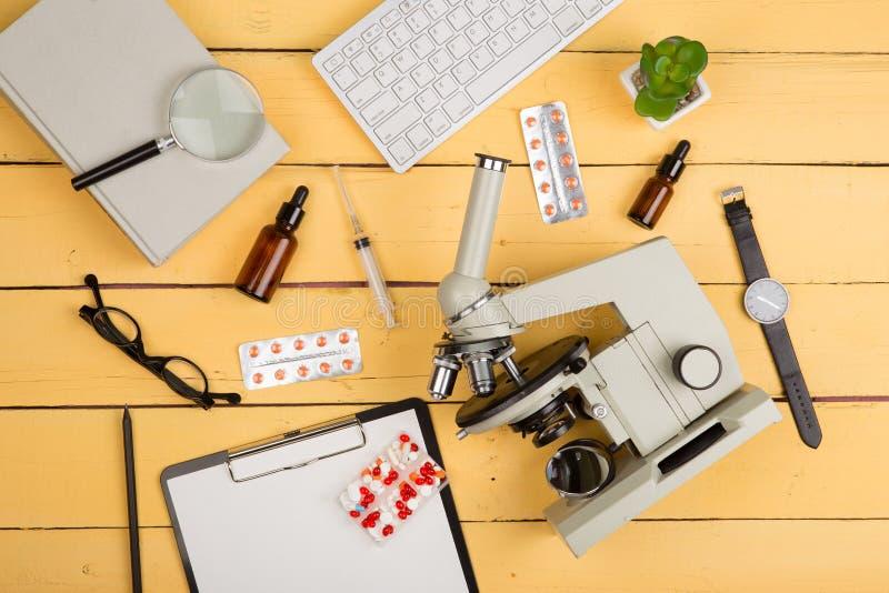 Onderwijs en wetenschapsconcept - microscoop, boek, het overdrijven gla stock afbeelding