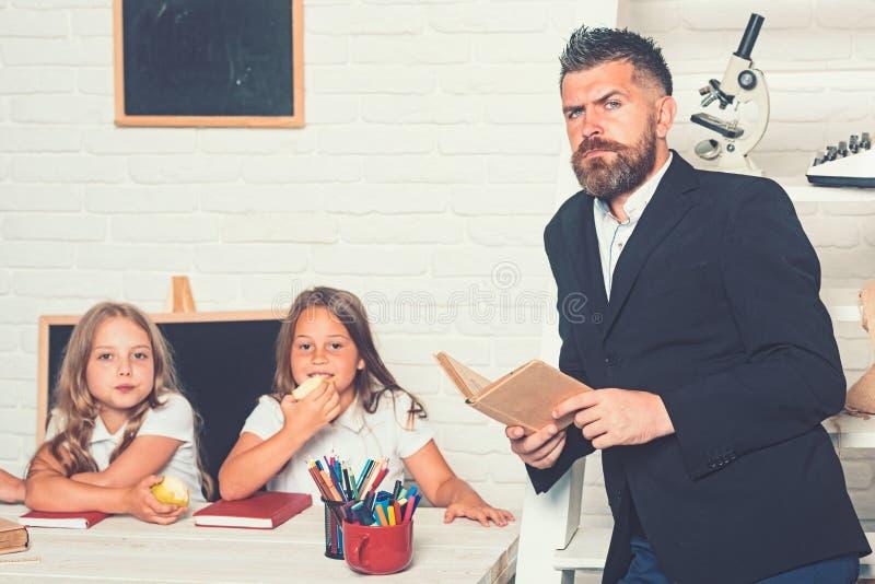 Onderwijs in kennisdag Van de literatuurles en lezing grammaticaboek Schooltijd van zusters en vader in bibliotheek stock foto's