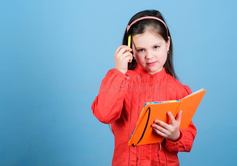 Onderwijs in lezing Het leuke meisje leert lezing en het schrijven in oefenboek Aanbiddelijke kleine open kindholding stock fotografie