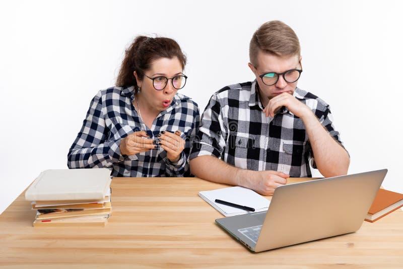 Onderwijs, studenten, mensenconcept - een paar tienerjaren in glazen zijn doen schrikken van iets tijdens het kijken in laptop stock fotografie