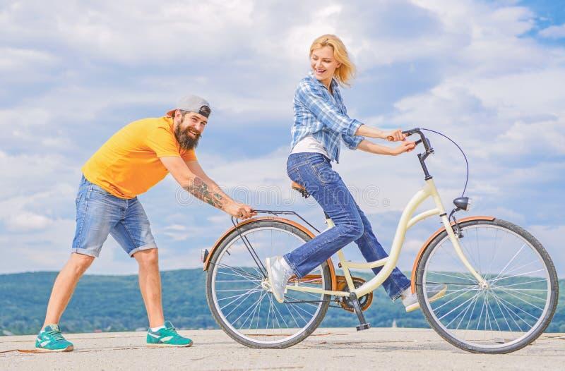 Onderwijs volwassene om fiets te berijden De mensenhulp houdt saldo en ritfiets Vind evenwicht De vrouw berijdt de achtergrond va stock afbeeldingen