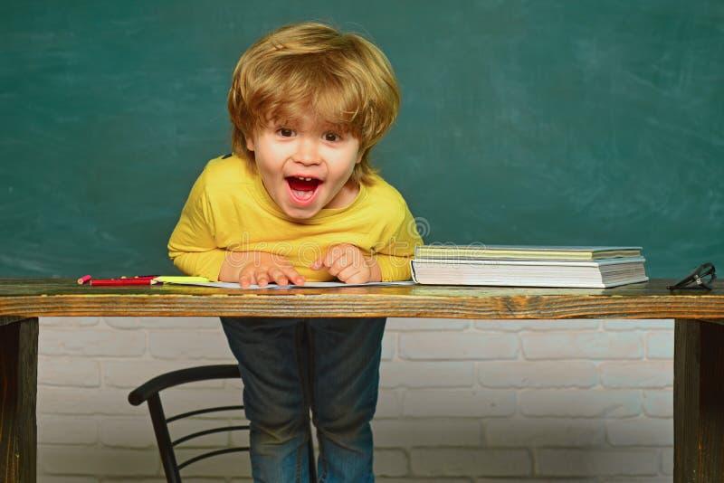 Onderwijs Vrolijk glimlachend kind bij het bord Hard examen schoolkind Gelukkige glimlachende leerlingen die bij het bureau trekk royalty-vrije stock foto's