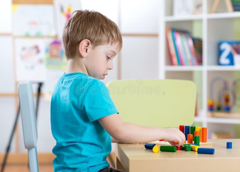 Onderwijsbeeld van kleuterschool Kindjongen het spelen met speelgoed bij lijst stock afbeeldingen